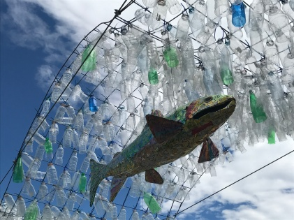 Fish in a river, the water made out of plastic bottles